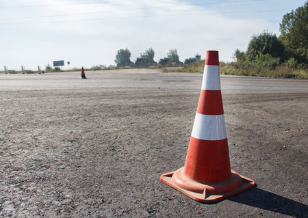 traffic cone, with white and orange stripes on gray asphalt, copy space. Stock fotó