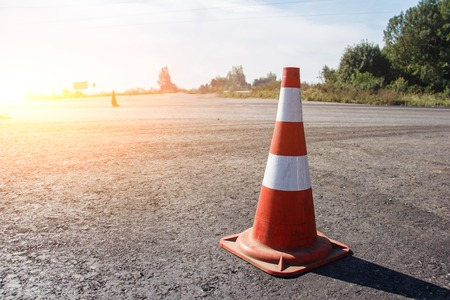 traffic cone, with white and orange stripes on gray asphalt, copy space. Archivio Fotografico - 118032728