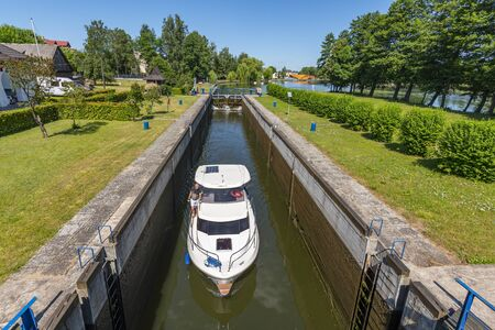 Boat entering gateway sluice (locks) on the Augustow Canal, Poland.