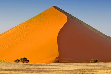 Sharp border of light and shadow over the crest of the dune at sunrise at Sossusvlei Namib Desert, Namib Naukluft National Park of Namibia. Фото со стока