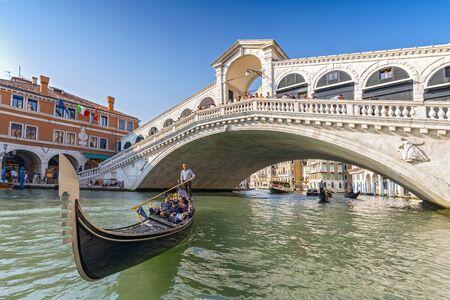 Gondolier rowing a tourist family in gondola in front of the Rialto Bridge in Venice, Italy.
