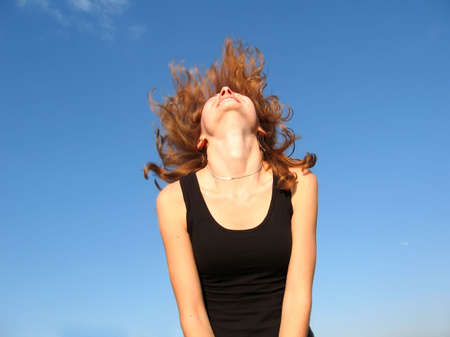 exuberance: Happy blonde girl posing outdoor with sky as background