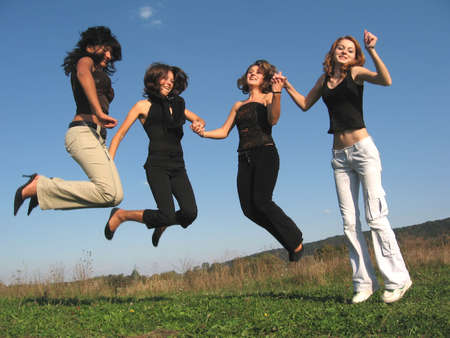 Beautiful women jumping altogether Stock Photo