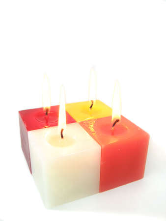Four colored candles burning - isolated over white