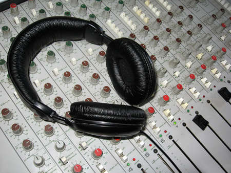 Headphones laying on a radio mixer in a studio