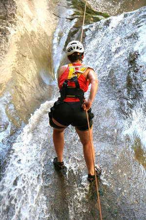 Woman in red climbing a waterfal - outdoor extreme photo