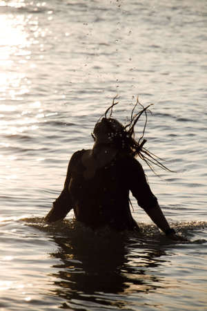 Happy woman playing in the sea during sunrise Stock Photo - 5499775