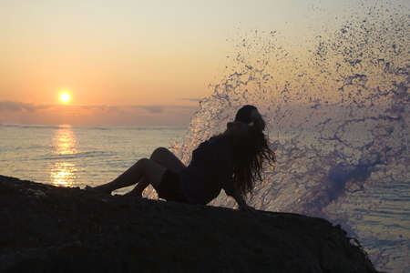 Woman sitting an the beach in sunrise Stock Photo - 5499771