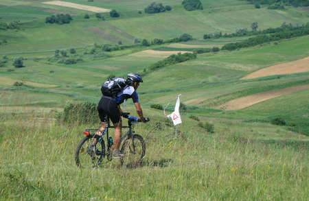 Cyclist on a byke on a hill in summer sunny day Stock Photo - 6183734