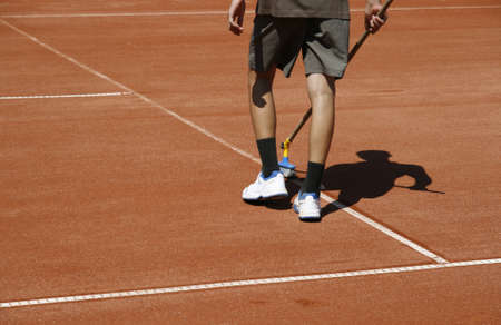 Young man cleaning lines of a court before competition photo