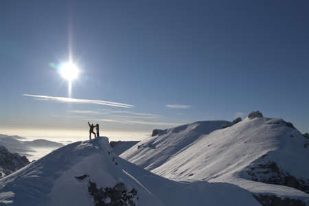 adventure holiday: Young man on mountain top with snowboard in Bucegi mountains, Romania