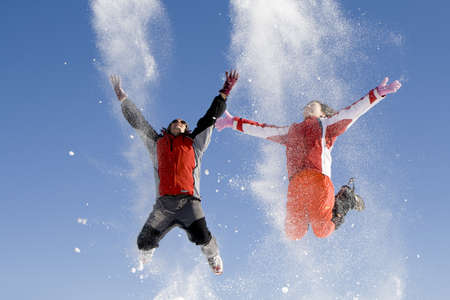 skier jumping: Young couple playing with snow outdoor in a sunny day Stock Photo