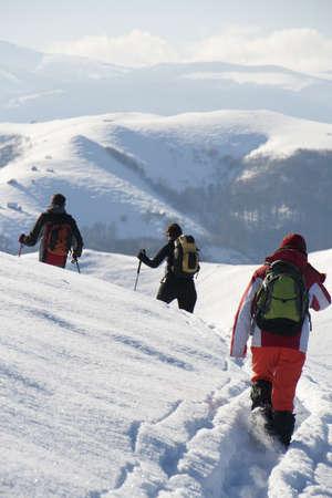 Teenagers walking on a new path through snow in the mountains