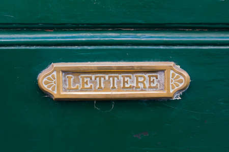 lettre: Old brass letterbox on a green door