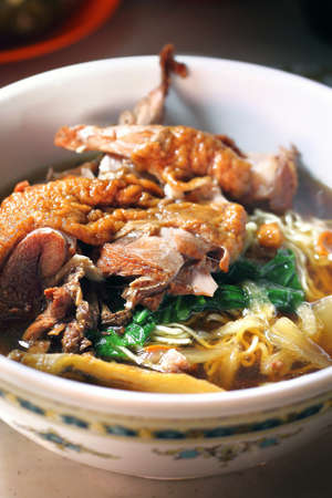 Wanton noodles with duck meat in white bowl