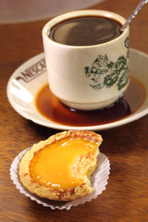 Typical chinese egg tarts with a cup of coffee in the background