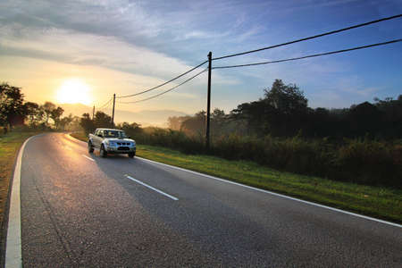 Car on country road at sunrise