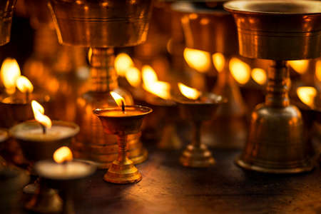Butter lamps with flames in the temple of Thamel, Nepal