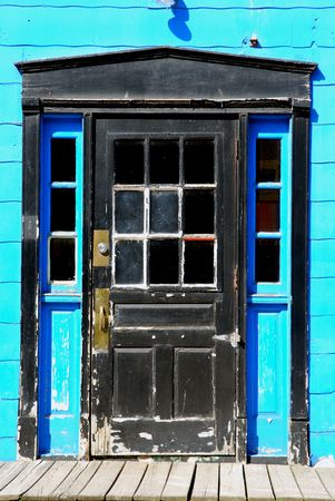 keylock: Old black wood door with windows and turqoise walls