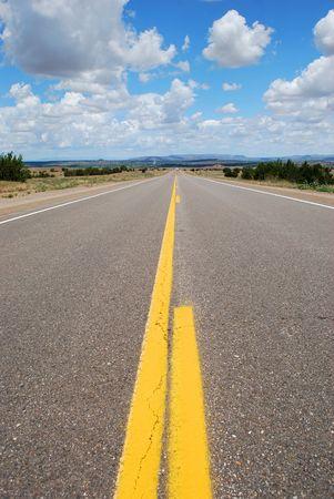 Long asphalt road with a cloudy sky photo