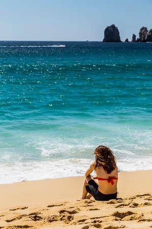 Woman Sitting in Bikini Relaxing on Sandy Beach