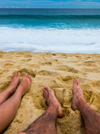 sit: Couples Feet on the Sand Together at Beach