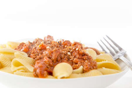 homestyle: bowl of fresh pasta noodle and bolognese meat and tomato sauce in homestyle meal on bright background Stock Photo