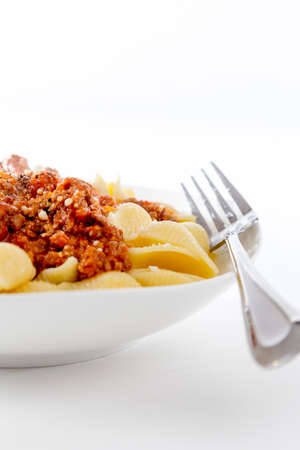 bowl of fresh pasta noodle and bolognese meat and tomato sauce in homestyle meal on bright background Фото со стока