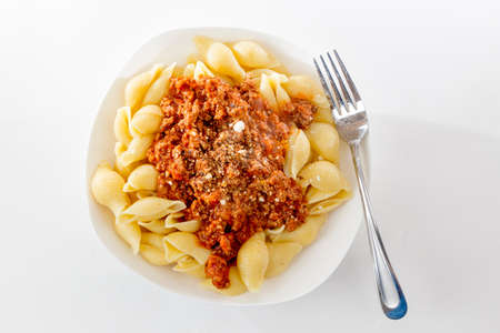 bowl of fresh pasta noodle and bolognese meat and tomato sauce in homestyle meal on bright background 免版税图像