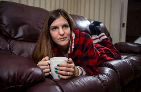 pyjama: Woman in Red Plaid  Pyjama Relax on Couch Stock Photo