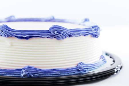 Cake with plain frosting and space for text on a bright background 免版税图像