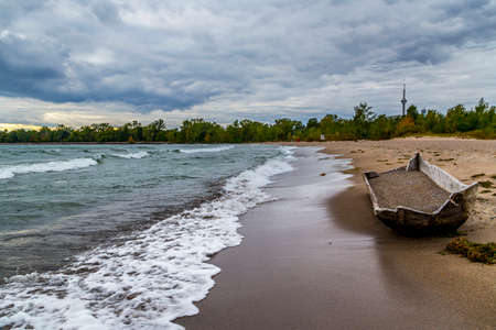 sandy beach view with old hand carved boat from tree log