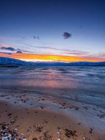 湖の岸から水に沈む夕日 写真素材