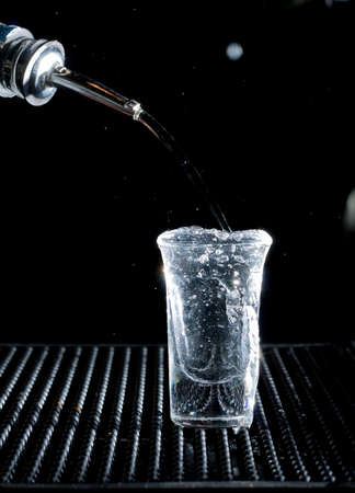 bartend: pouring into a shot glass
