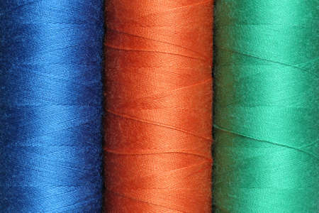 Three spools of color polyester threads
