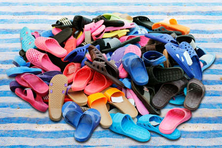 Piles of shoes sold in various color combinations rural land market, sandals, casual shoes, old.