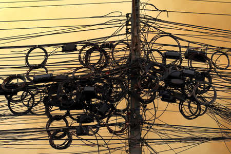 High-voltage power cord, wire tangle electrical energy on sky background evening atmosphere Foto de archivo