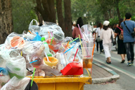 Garbage plastic Waste trash full of trash bin yellow and background people are walking on the sidewalk garden, Garbage bin, Trash plastic pollution, Garbage, Waste, Plastic Waste Stockfoto