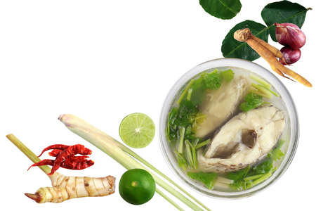 Boiled tilapia fish in clear bowl and Ingredients curry on white background (Tom-yam-pla thai word), Piece slice fish soup spicy in cup, Thai food tilapia fish boiled hot and sour soup