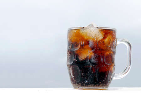 black cola soda in glass with ice cubes for refreshments feel, beverage cola and cubes ice refreshing cool in glass on grey background