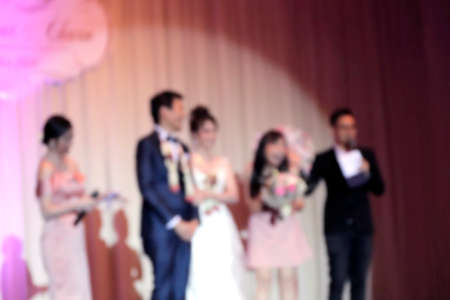 blurred bride and groom in stage lights, wedding event party in hall room for background, wedding celebration dinner blur image