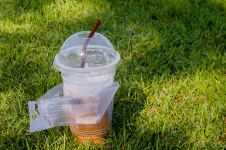 plastic cup waste and straw tube used, garbage waste plastic on grass floor