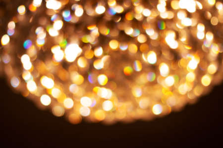 yellow gold glowing bokeh light for luxurious background, golden shiny light sparkle background, christmas glitter background gold color in dark night