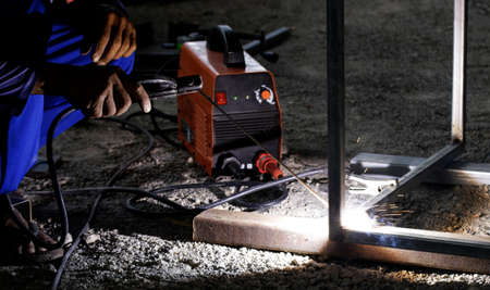 welder and welding sparks, construction and metal work industrial concept, metal welding with sparks, laborer or labor day concept
