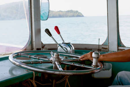 steering wheel ship and hand of boat driver inside the boat, steering wheel ship with hand holding, navigation console with metal steering wheel inside the motorboat travel at thailand Stok Fotoğraf