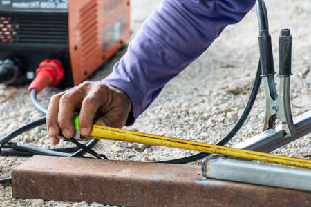worker welder are holding tape measure in welding work, construction and metal work industrial concept, laborer or labor day concept Stok Fotoğraf