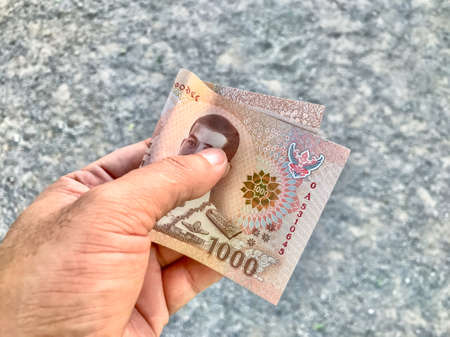 money banknote thai 1000 baht in hand are holding, savings money, giving or donate concept