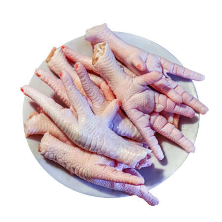 chicken feet uncooked in a plate, chicken paw isolated on white and top view