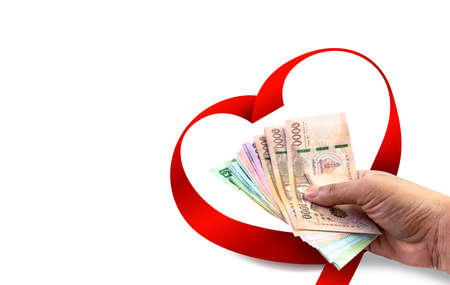 money in hand and ribbon heart for valentine's day, money for charity donation, giving money concept, money banknote thai baht and red ribbon heart shape, copy space