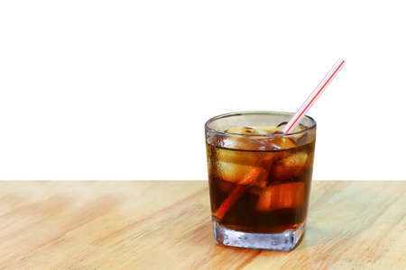 cola glass on table plank, cola with ice cubes in the glass
